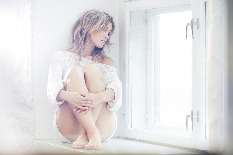 eine Frau, die auf dem Fensterbrett sitzt und nachdenkt