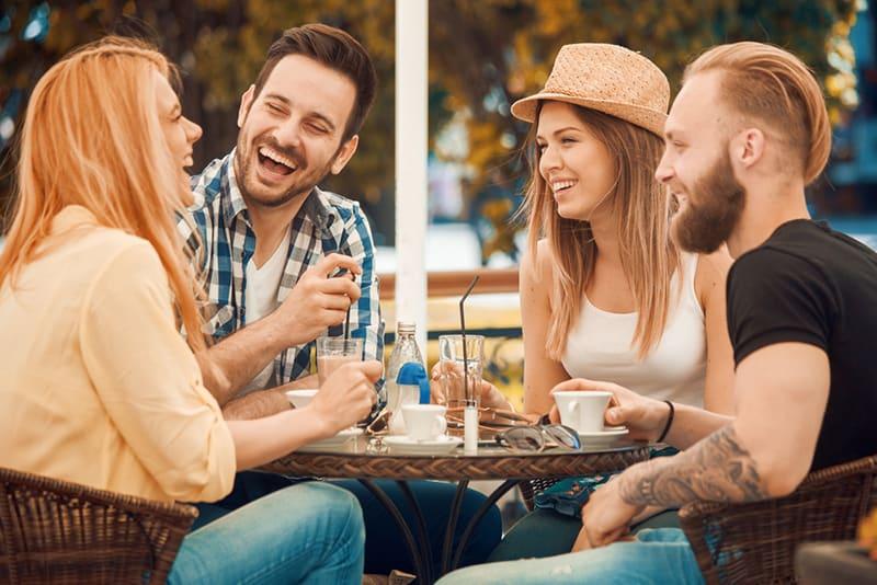 Eine Gruppe von Freunden lacht, während sie im Café sitzen