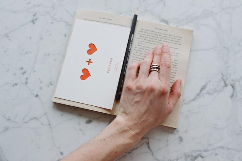 eine Person, die Hand auf einem Buch mit Grußkarte darauf hält