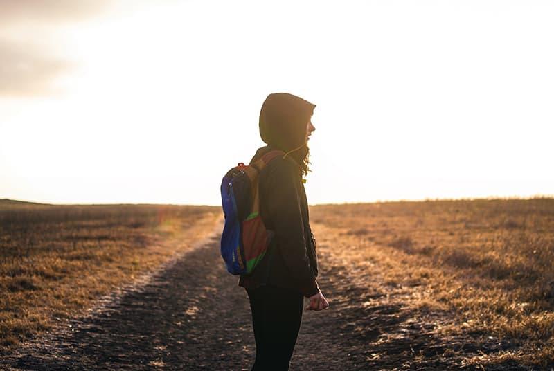 eine Person, die während des Sonnenuntergangs allein auf der Straße steht