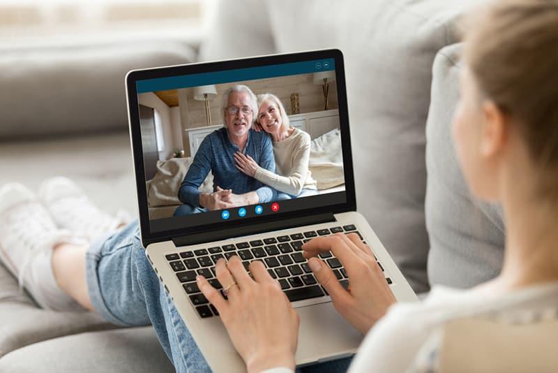 Eine Tochter, die mit ihren Eltern einen Videoanruf auf dem Laptop hat, während sie auf der Couch sitzt