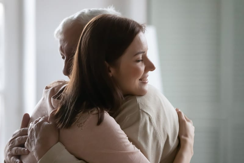 Eine Tochter und ein Vater umarmen sich im Haus