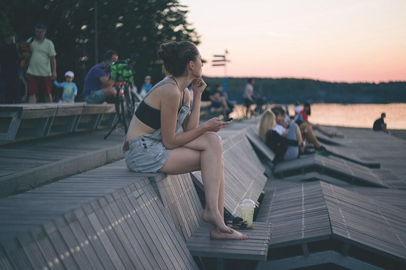 eine barfüßige Frau, die auf der Holzbank sitzt und den Sonnenuntergang beobachtet