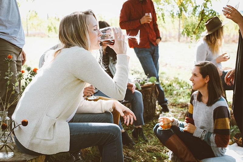 eine blonde Frau, die Wein auf der Party im Freien trinkt