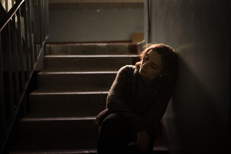 eine depressive Frau, die auf der dunklen Treppe sitzt