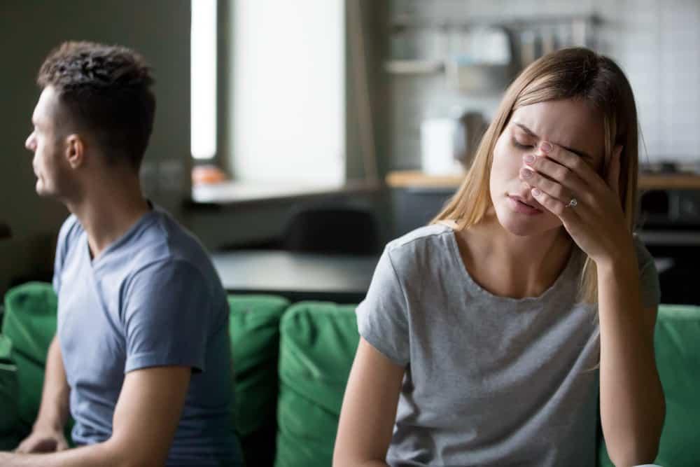 eine enttäuschte Frau, die nach einem Streit neben ihrem Mann auf der Couch sitzt