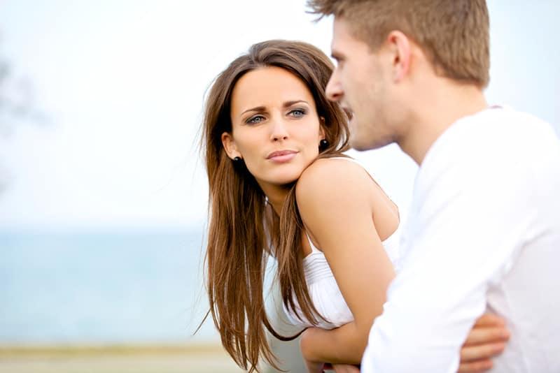 eine ernste Frau, die einen Mann ansieht, der mit ihr spricht, während beide sich auf den Zaun lehnen