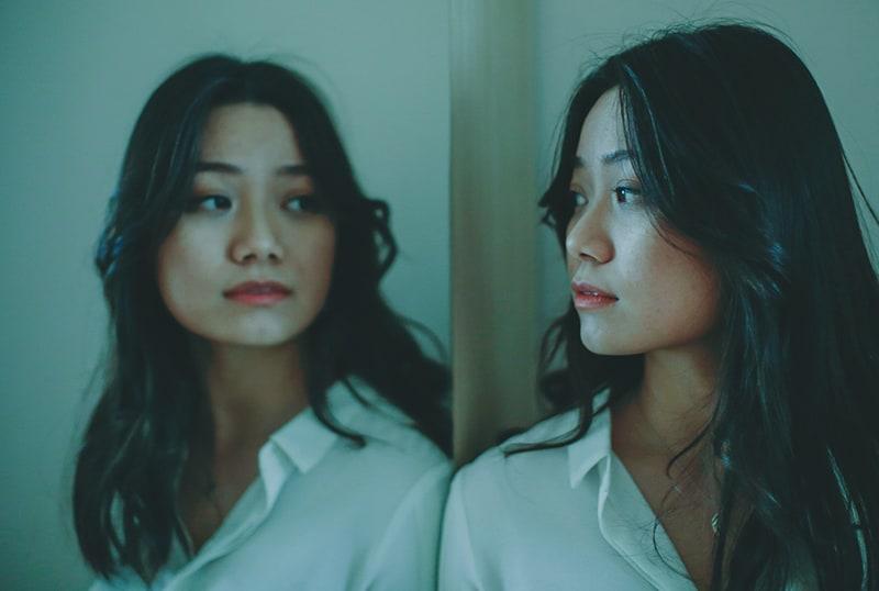 eine ernste Frau, die sich in den Spiegel schaut, während sie sich darauf stützt