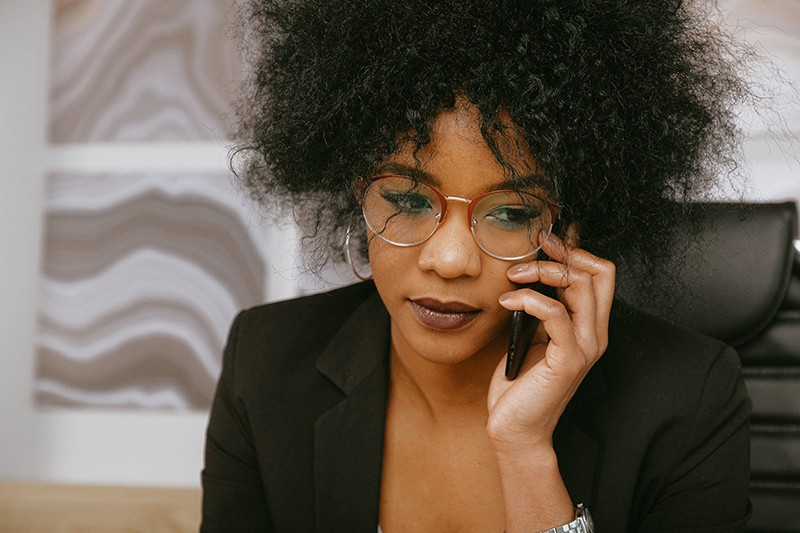 Eine ernsthafte Frau, die versucht, jemanden am Telefon zu erreichen, während sie im Büro sitzt