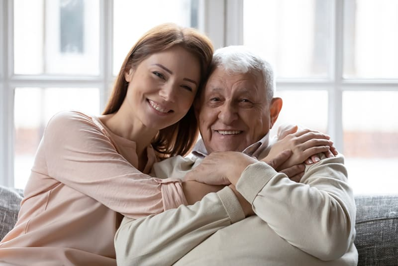 Eine erwachsene Tochter umarmt ihren Vater, während sie auf der Couch sitzt