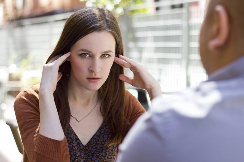 Eine gelangweilte Frau berührt ihren Kopf, während sie mit einem Mann im Café sitzt
