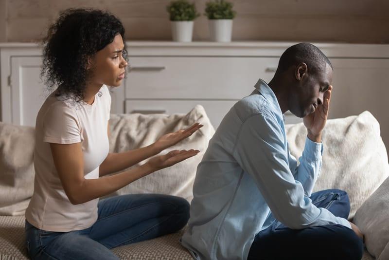 eine gestresste Frau, die versucht, mit einem frustrierten Mann zu sprechen, während sie auf der Couch sitzt