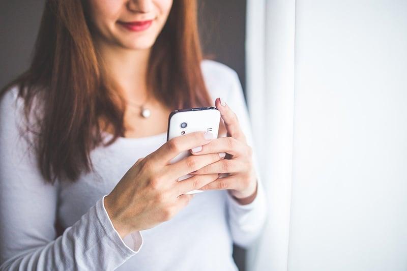 eine lächelnde Frau, die auf dem Smartphone tippt, das nahe dem weißen Vorhang steht