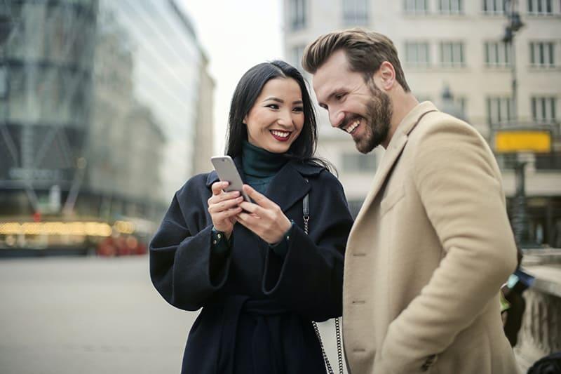 eine lächelnde Frau, die einem lächelnden Mann ein Smartphone zeigt, während sie auf der Straße steht