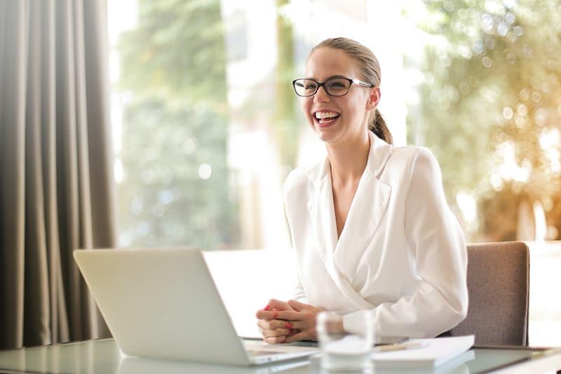 eine lächelnde Frau, die im Büro am Schreibtisch sitzt
