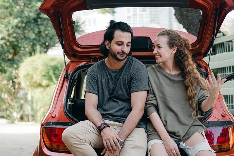 eine lächelnde Frau, die mit einem Mann spricht, der in den Boden schaut, während er auf dem Autokofferraum sitzt