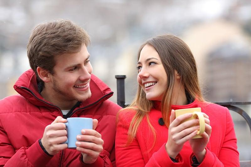 eine lächelnde Frau, die zu einem lächelnden Mann schaut, der ihr Kompliment macht, während sie zusammen Tee im Freien trinkt