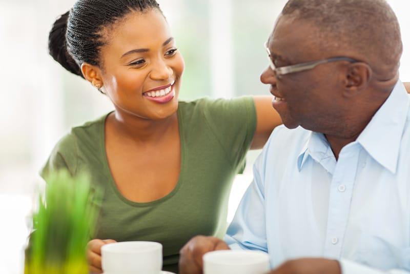 eine lächelnde Tochter und ein Vater schauen sich an, während sie zusammen Kaffee trinken