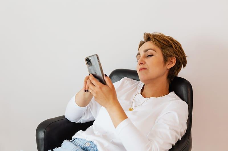 eine nachdenkliche Frau, die ein Smartphone betrachtet, während sie im Sessel sitzt