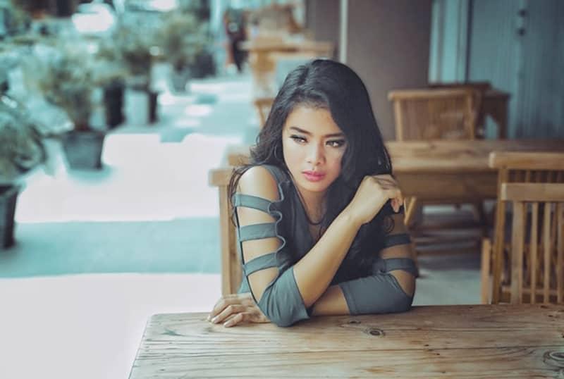 eine nachdenkliche Frau, die alleine am Tisch sitzt und zur Seite schaut