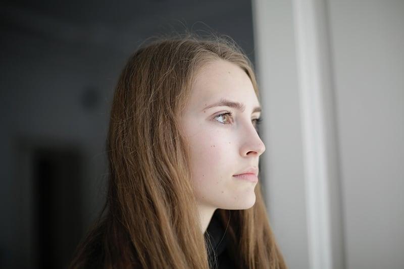 eine nachdenkliche Frau, die in der Nähe des Fensters im Raum stand