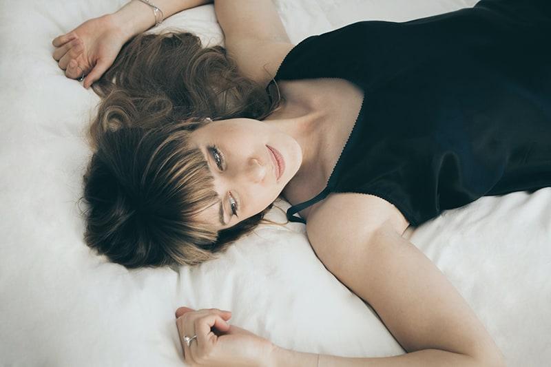 eine nachdenkliche Frau, die mit weißen Laken auf dem Bett liegt
