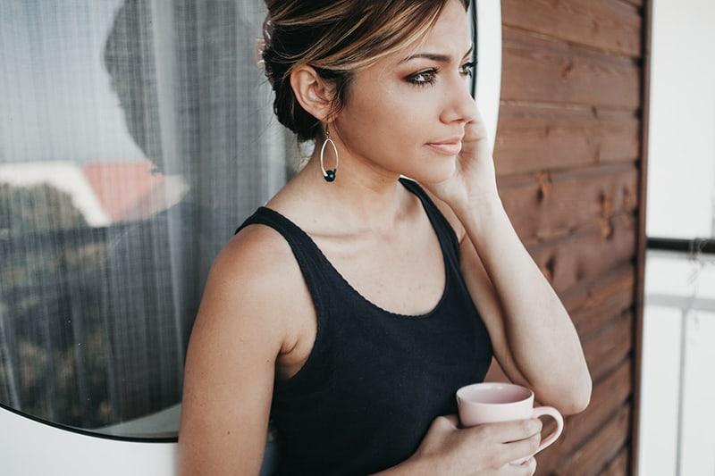 eine nachdenkliche Frau, die eine Tasse Kaffee hält, während sie auf dem Balkon steht