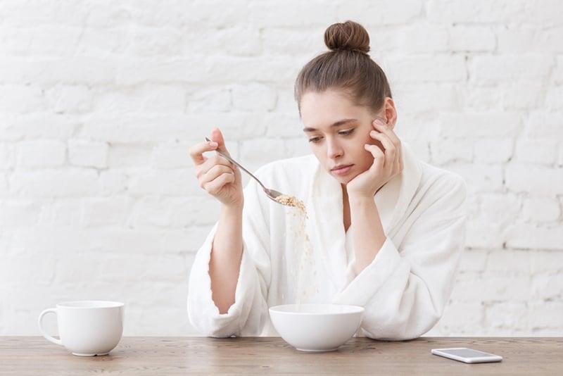 Eine nachdenkliche Frau, die während des Frühstücks einen Löffel hält, hat keinen Appetit