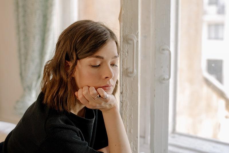 eine nachdenkliche Frau, die sich ans Fenster lehnt und nach unten schaut