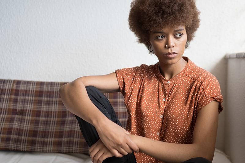 eine nachdenkliche Frau, die beiseite schaut, während sie auf der Couch sitzt