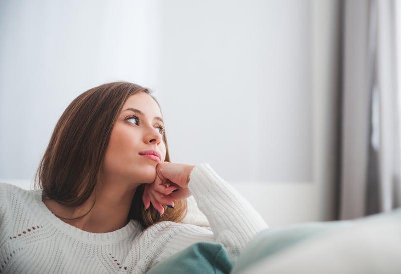 eine nachdenkliche Frau, die auf dem Sofa sitzt und zur Seite schaut