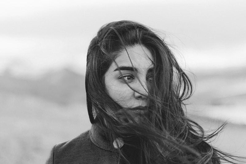eine pessimistische Frau, die beiseite schaut, während sie auf dem Wind steht