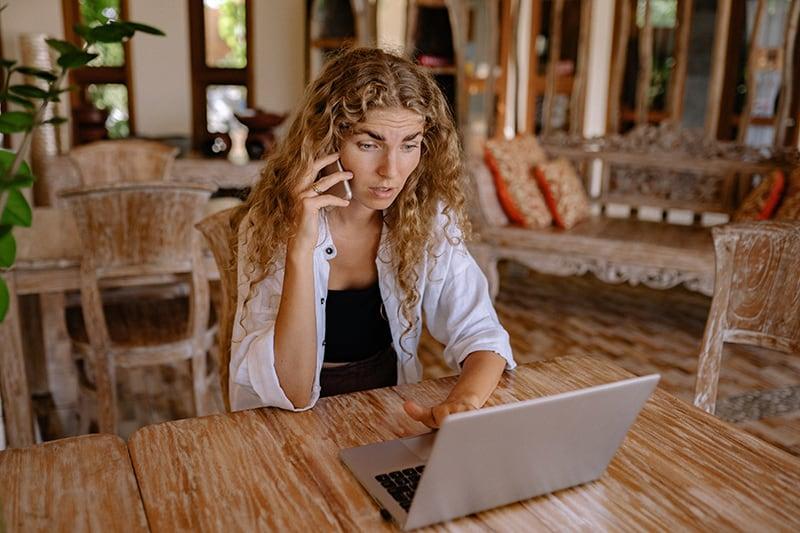 eine stressige Frau, die digitale Geräte benutzt, während sie am Tisch sitzt