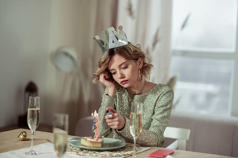 eine traurige Frau, die ein Feuerzeug benutzt, um Kerzen auf einer Geburtstagstorte abzufeuern