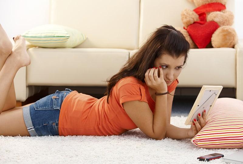eine traurige Frau, die ein Foto ihres Ex-Freundes schaut, während sie auf dem Teppich liegt