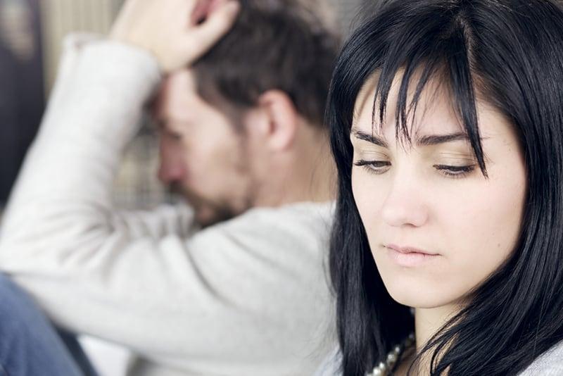 eine traurige Frau, die nach unten schaut, während sie neben einem Mann sitzt, der verärgert aussieht