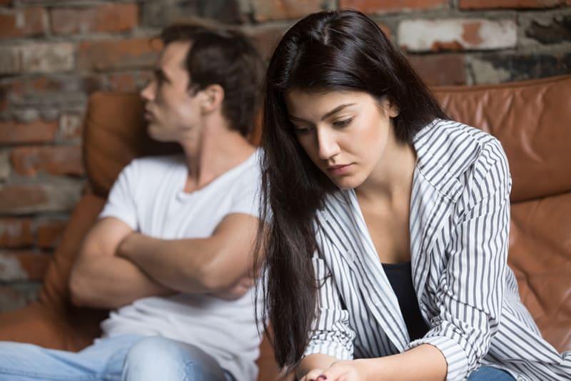 eine traurige Frau, die nach unten schaut und über die Beziehungsprobleme nachdenkt, während ihr Mann hinter ihr sitzt