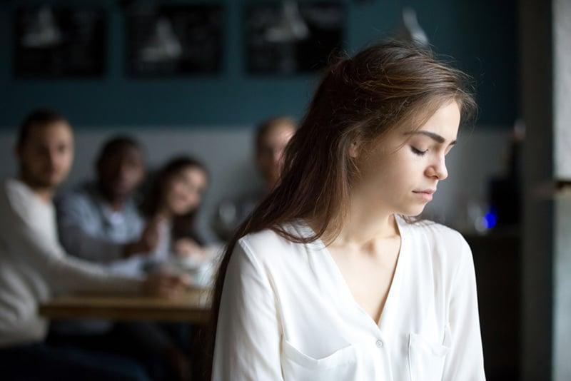 eine traurige Frau, die schlechte Freunde ignoriert und getrennt von ihnen sitzt