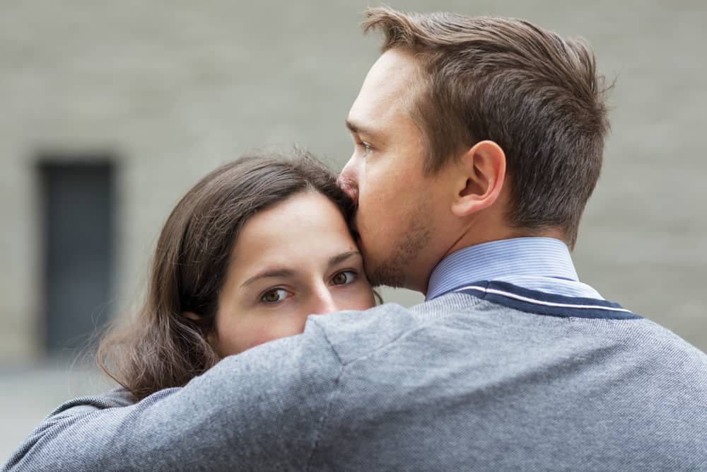 eine traurige Frau in den Armen eines Mannes, der sie auf den Kopf küsst