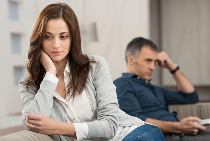 eine traurige Frau, die auf der Couch neben einem Mann sitzt, der eine Fernbedienung hält