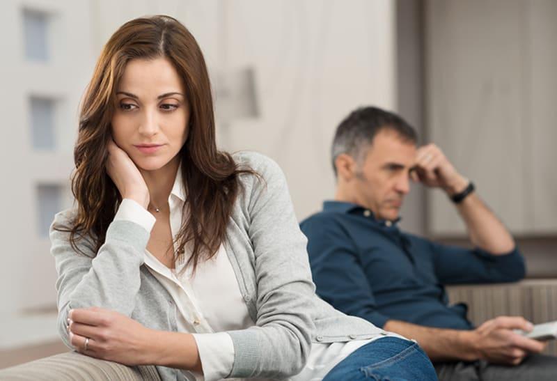 eine traurige Frau, die auf der Couch sitzt, während ein Mann neben ihr fernsieht