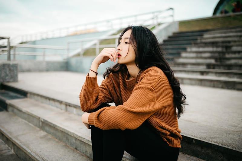 eine traurige Frau sitzt auf der Treppe und berührt die Lippen mit der Hand