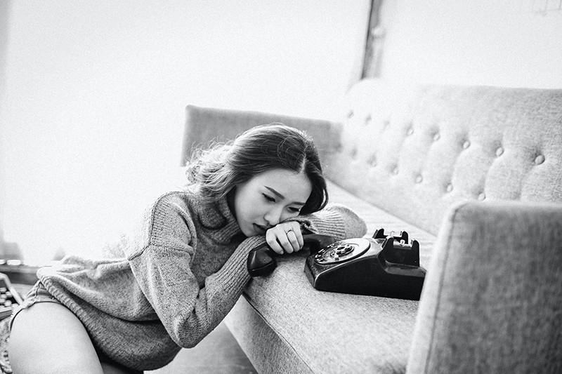 Eine unsichere Frau hält das Telefon und lehnt sich auf das Sofa