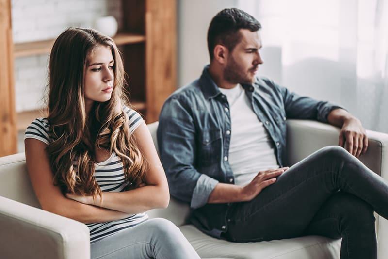 eine verärgerte Frau, die neben ihrem Freund auf dem Sofa sitzt