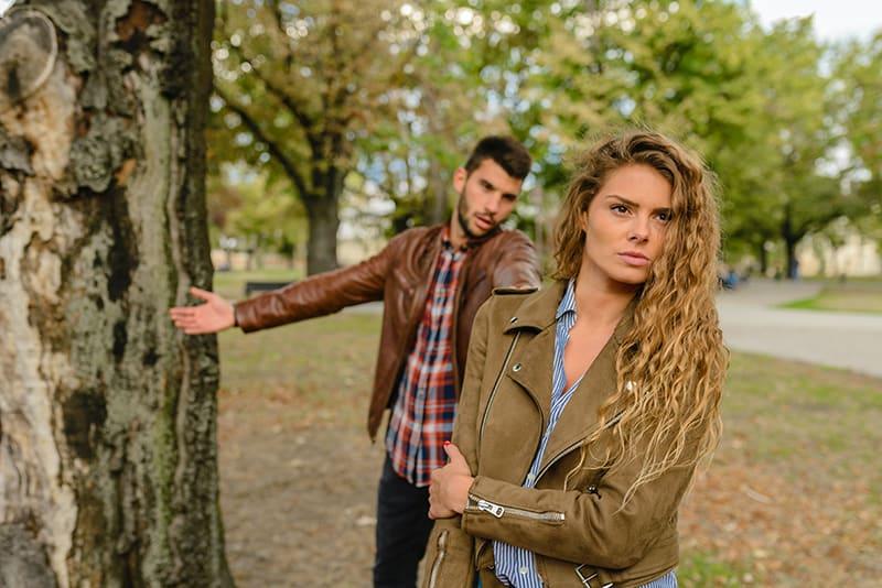 eine verärgerte Frau, die vor ihrem Freund steht und mit ihr im Park streitet