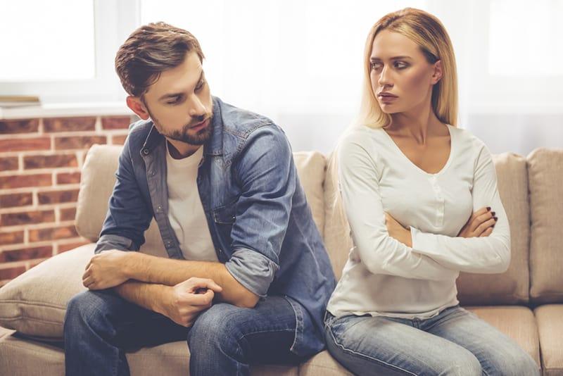 eine verärgerte Frau und ein gleichgültiger Mann, die sich auf der Couch ansehen