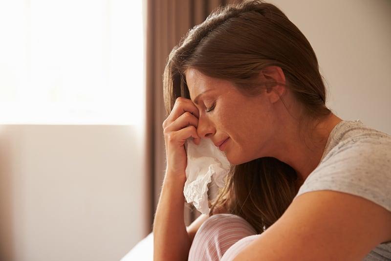 eine weinende Frau, die ein Papiertaschentuch hält und auf dem Bett sitzt
