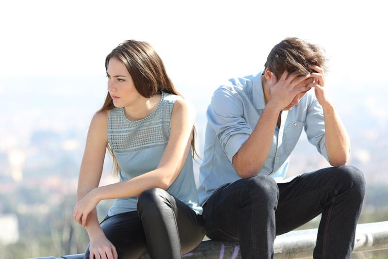 eine wütende Frau, die neben einem Mann sitzt, der Gesicht mit Handflächen auf dem Dach bedeckt