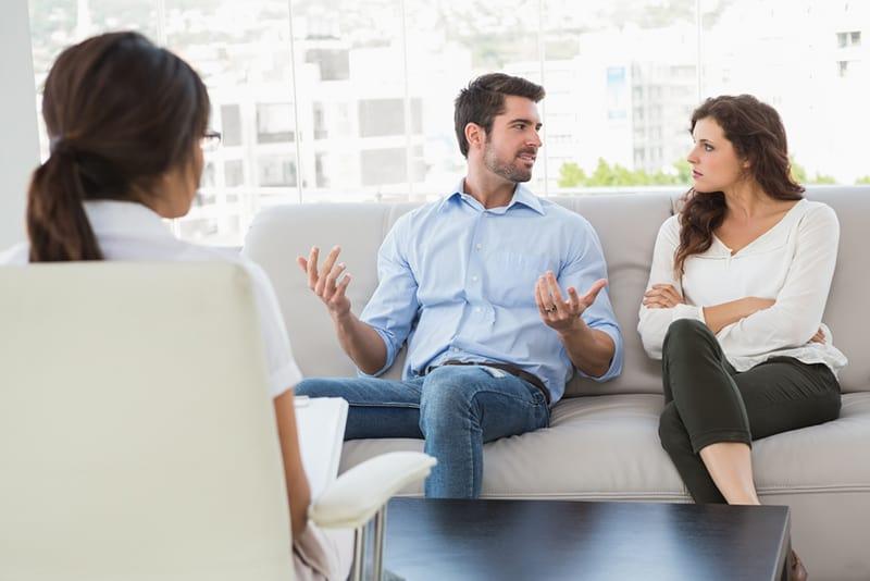 eine wütende Frau mit verschränkten Armen, die ihrem Ehemann zuhört, während sie auf der Couch beim Eheberater sitzt