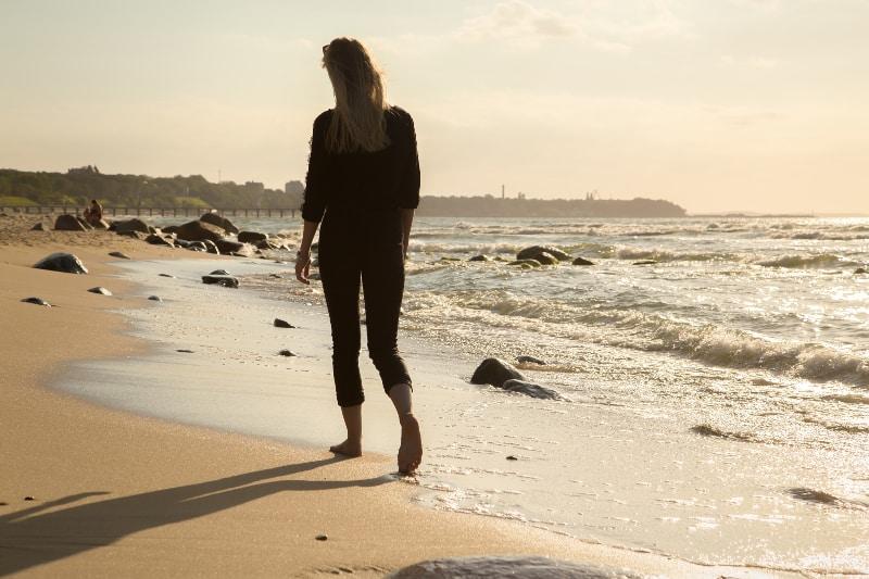 einsames Mädchen setzt am Strand